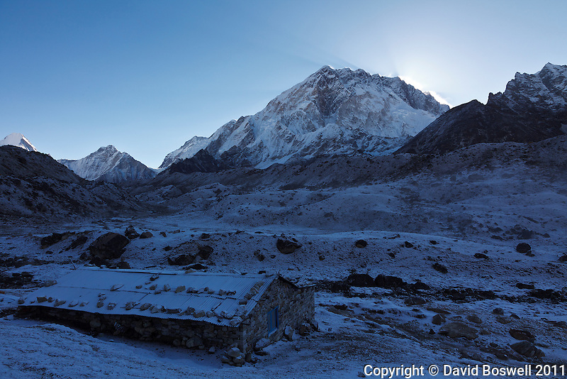The sun rises behind the summit of Nuptse as a light snow blankets the village of Lobuche in the Khumbu Valley region of Nepal.
