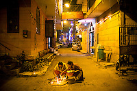 Two women lights candles in a street in New Delhi on the occasion of Diwali, one of the biggest festival for Hindus.