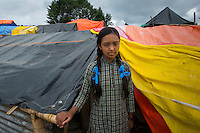 Nepal, Dholakha, Charikot earthquake relief work. The NGO Loom, unpacking supplies in the hard hit Dolakha region near the second epicenter. They have a $5000 TEWA funded grant (through Global Fund for Women) and are using it to hand out mosquito nets, buckets and dignity kits for women with newborn children. These kits include tootpaste, lentils, rice, baby massage oil, baby clothes, baby food, sanitary pads, a shawl. Surveying the extent of the earthquake damage in town. Displaced girl emerges from her tarp/tent ready for school.