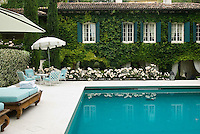 The outdoor swimming pool is enclosed by a variegated hedge and a wing of the ivy-clad property