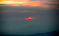 Sun setting, dense smoke cloud from forest fires, Colorado. June 2013