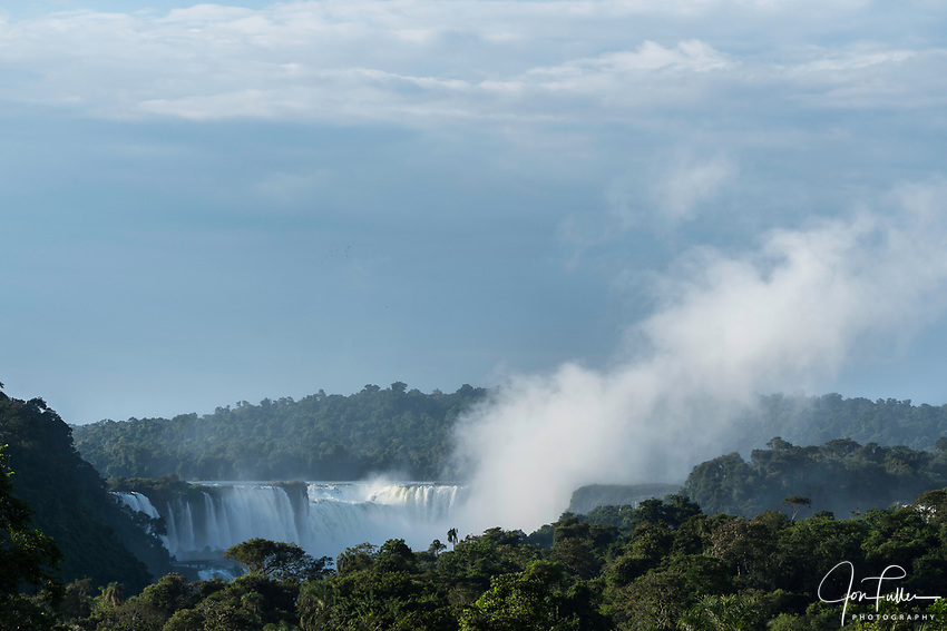 A plume of mist rises from the Devil's Throat or Garganta del Diablo at sunrise at Iguazu Falls National Park in Argentina.  A UNESCO World Heritage Site.  Brazil is on the left side of the canyon, with Argentina on the right.