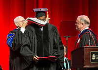 NWA Democrat-Gazette/BEN GOFF @NWABENGOFF<br /> Dr. Joe Steinmetz (left), chancellor of the University of Arkansas, and Mark Waldrip (right), vice chairman of the university board of trustees, present an honorary degree to songwriter and record producer Al Bell Saturday, May 11, 2019, during the University of Arkansas all university commencement ceremony in Bud Walton Arena in Fayetteville.
