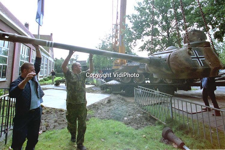 Foto: VidiPhoto..SCHAARSBERGEN - Militairen zijn dinsdag in Schaarsbergen een halve dag bezig geweest om twee tanks uit de Tweede Wereldoorlog te verplaatsen. Het historische oorlogstuig naast het Oorlogsmuseum '40-'45 moest weg van de gemeente Arnhem, omdat de tanks op het huis van een buurvrouw gericht waren. Zij vond dat te bedreigend. Doordat de geschutskoepels niet meer gedraaid konden worden, was verplaatsing van de Duitse T34 en de Amerikaanse Sherman nodig. De Duitse tank komt nu aan de voorkant van het museum; het Amerikaanse pantservoertuig gaat naar Engeland.