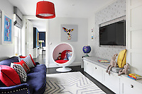 A colourful playroom adjoins the reception room, furnished with a retro egg chair, sofa, bright red cushions and practical built-in storage. A flat screen television hangs on a wall papered with a treature map design