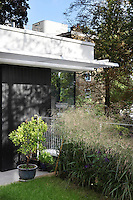 A garden detail with a border planted with grasses outside a modern house with a panelled facade.