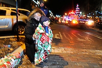 NWA Media/ J.T. Wampler -Ronni Harding of Rogers watches the holiday floats pass Monday Dec. 1, 2014 while keeping her grandson Tristan Sliva warm during the Rogers Christmas parade sponsored by Main Street Rogers. Rockin' Around the Christmas tree was this year's theme. Around 100 entries participated in the parade.