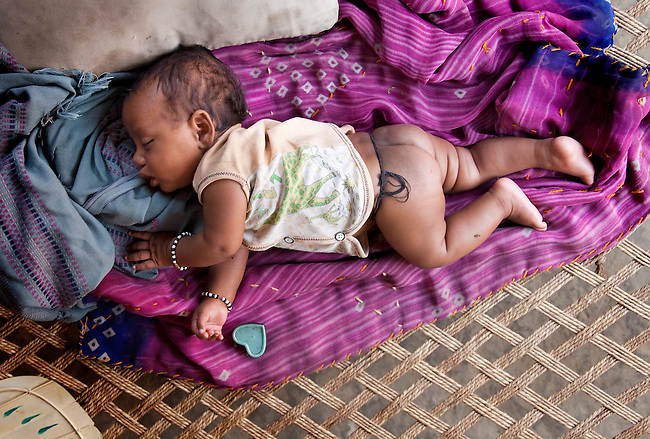 Papu Kumari (2months old) lies on a charpoy, or rope bed, at home in Bhagwanpuri Raiti village near to the local Anganwadi health clinic where oral rehydration salts (ORS) and zinc tablets are given out to combat the sometimes fatal effects of diarrhea.The village located in Vaishali district outside Patna in Bihar, India has been rolling out the ORS and Zinc program as part of the IKEA Social Initiative to combat child mortality rates caused by diarrhea. It is proving to be very successful with education and support provided by local nursing staff, health activists  and program officers from UNICEF. The treatment is a 14 day course administering diluted oral rehydration salts and a zinc tablet which is more effective than salts alone in combating the effects of severe diarrhea. Picture by Graham Crouch/UNICEF