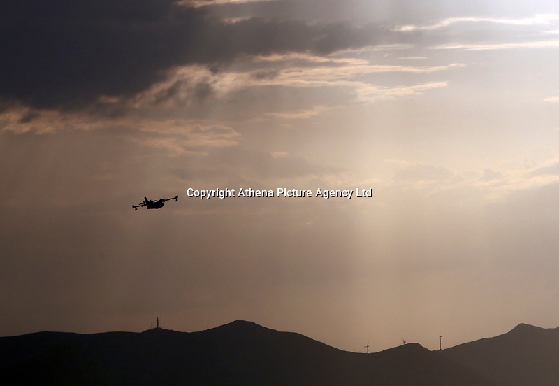 Pictured: A Canadair fire aircraft flies over the Mati area, Kokkino Limanaki near Rafina, Greece. Tuesday 24 July 2018<br /> Re: Deaths caused by wild forest fires throughout Greece.