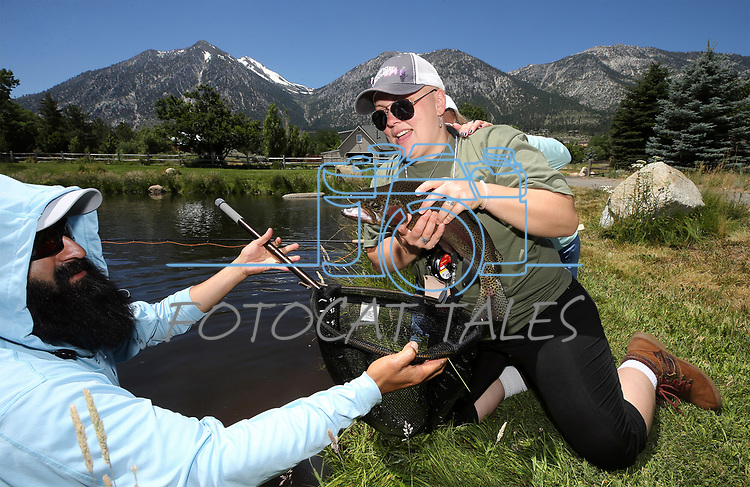Fishing guide Jose Luna helps cancer survivor Chelle Futch release her catch during a Casting for Recovery retreat in Gardnerville, Nev., on Friday, June 30, 2017. <br /> Photo by Cathleen Allison/Nevada Photo Source
