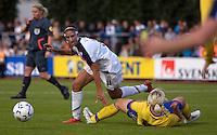 Carli Lloyd (11) avoids the slide tackle from Sweden's Charlotte Rohlin, during the match against Sweden, Landskamp, Sweden, July 5th, 2008.