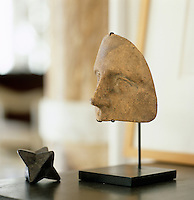 A detail of a half mask and an artifact on display in the study