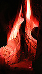 With a red light from below and white light from above the walls of the cave appear to be aflame.