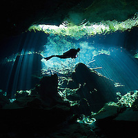 RX0622-Ds. scuba diver (model released) swims between curtains of light shining down through the opening to a cenote, the entranceway to caverns and tunnels waiting to be explored. Riviera Maya, Yucatan Peninsula, Mexico. Cropped to square from native horizontal format.<br /> Photo Copyright &copy; Brandon Cole. All rights reserved worldwide.  www.brandoncole.com