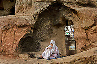 Hazara woman embroidering in front of the cave where she lives.