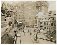 Construction of the central section of the Chateau Frontenac, photograph, 1921, from the Archives of the Chateau Frontenac, Quebec City, Quebec, Canada. The Chateau Frontenac opened in 1893 and was designed by Bruce Price as a chateau style hotel for the Canadian Pacific Railway company or CPR. It was extended in 1924 by William Sutherland Maxwell. The building is now a hotel, the Fairmont Le Chateau Frontenac, and is listed as a National Historic Site of Canada. The Historic District of Old Quebec is listed as a UNESCO World Heritage Site. Copyright Archives Chateau Frontenac / Manuel Cohen