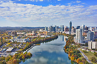 Another aerial view of Austin skyline from higher that captures the downtown and all the high rise buildings hugging the shoreline of Lady Bird Lake with the city in view. Again the water had this nice reflection of the clouds and high rise buildings reflected in the water along with the wonderful fall colors in the trees along the banks. This image capture this urban landscape of the Austin Skyline from the east side and shows some of the citys tallest buildings like the Austonian, with the top of the Frost just barely peeking above the crowd along the shoreline. Until they finish the Independent the Austonian will remain the tallest in town at least for another year or more.  Austin is the fastest growing city in the US and the 11th most populous city and is the seat of the Texas State Capitol. At the last census this urban city had a population of just over 947,000 and growing.