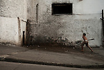 A boy playing baseball in the street in Santiago de Cuba.