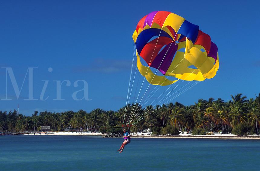 Person parasailing above Atlantic Ocean near beach at Cheeca Lodge Resort, Florida Keys. Islamorada, Florida.