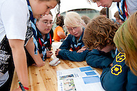 Reading the camp magazine is one good thing scouts are doing while it's raining. Photo: Christoffer Munkestam/Scouterna