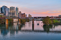 Austin cityscape with railroad track over Lady Bird Lake with all the high rise condos, and office building hugging the shoreline of the lake as the sun set added some color to the sky and waters.. Austin has been in a big growth spurt along this part of the lake so it has been impossible to capture images from here because of all the cranes.  Now some of those buildings and high rise buildings has been finished.  However there are still plenty of cranes  just an inch over and you would see many more.  You can see Austins tallest high rise for now the Austonian along with the W hotel, Four Season Residence,