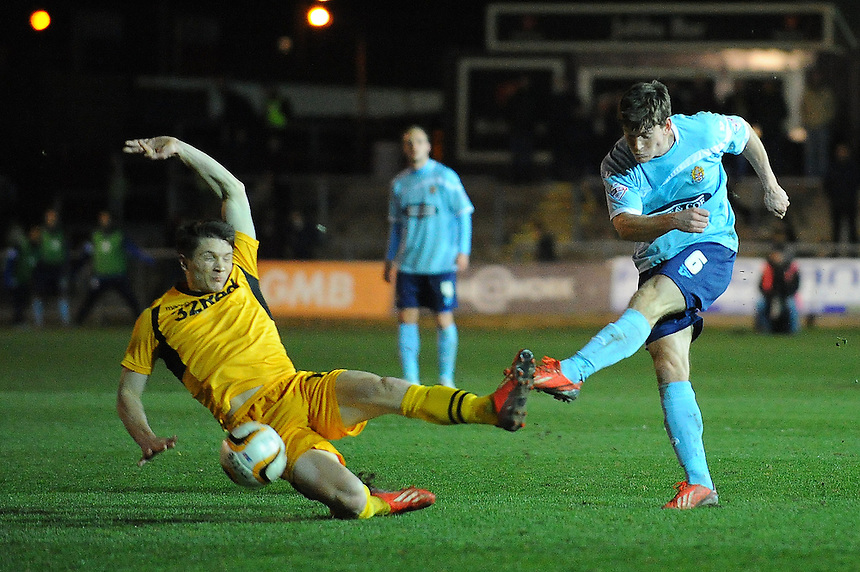 Dagenham and Redbridge's Billy Bingham shoots under pressure from Newport County's Ryan Burge<br /> <br /> Photo by Kevin Barnes/CameraSport<br /> <br /> Football - The Football League Sky Bet League Two - Newport County AFC v Dagenham &amp; Redbridge - Wednesday 19th March 2014 - Rodney Parade - Newport<br /> <br /> &copy; CameraSport - 43 Linden Ave. Countesthorpe. Leicester. England. LE8 5PG - Tel: +44 (0) 116 277 4147 - admin@camerasport.com - www.camerasport.com