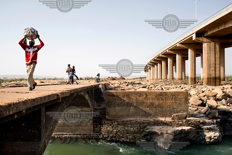 People cross an arch spanning a rivulet of the Niger River with the Chinese built bridge in the background. It was opened in September 2011 and is the third crossing of the Niger in Bamako.