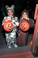 Siblings age 6 and 8 dressed as cat and monk for Halloween night out.  St Paul  Minnesota USA