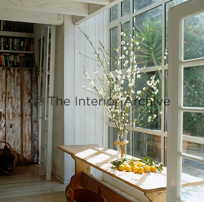 In this living rooom a simple flower arrangement of white blossoms in a glass vase creates a pleasing focal point on a wooden refectory table placed in front of a large glass window