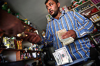 SYRIEN, 07.2014, Koreen (Provinz Idlib). Leben ohne Zentralregierung: Geldwechsel im Lebensmittelladen. In den Rebellengebieten gibt es kein Bankensystem mehr. Auch wenn die Inflation die Preise verdreifacht hat, ist die syrische Waehrung immer noch im taeglichen Gebrauch. Fuer grenzueberschreitende Geschaefte werden aber Dollar benoetigt. | Life without a central government: Money exchange in a grocery shop. There´s no bank system anymore available in rebel held areas. But Syrian currency is still in regular use for daily needs, though the inflation has tripled the prices. But in cross-border deals Dollars are used.<br /> © Timo Vogt/EST&OST