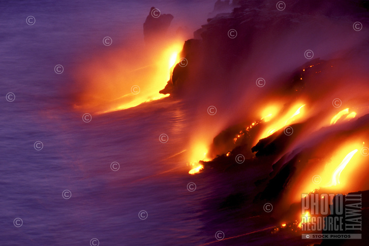 Fiery molten lava enters the sea at Volcanoes National Park, Hawaii.