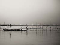 The Brahmaputra river that flows into India is wide enough to hold a few island towns. This image shows rustic fishing mechanisms used by villagers from the river islands.