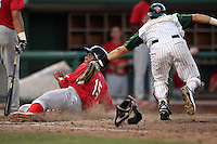 Quad Cities River Bandits outfielder Oscar Taveras #15 is tagged out by Fort Wayne TinCaps catcher Eammanuel Quiles #15 after trying to score from third when Quiles threw to second on a steal attempt from a runner on first during a game at Parkview Field on July 25, 2011 in Fort Wayne, Indiana.  Quad Cities defeated Fort Wayne 11-10.  (Mike Janes/Four Seam Images)