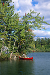 Red canoe at a waterfront campsite, Kezar Lake Camping Area, Lovell, Maine, USA