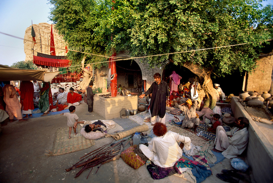 SEHWAN SHARIF, PAKISTAN - SEPTEMBER, 2006:  A group of devotees gather near Sehwan Fort to celebrate the annual Urs of Lal Shahbaz Qalandar, a 13th century Sufi Master worshiped alike by Hindus and Muslims. Born as Seyed Shah Hussain (Usman) Marandi, he later on titled as Lal (red) Shahbaz ( Falcon) Qalandar (as he belonged to Qalandria order of sufism).