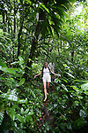 Woman hiking through rainforest and in creek near Titou Gorge