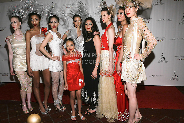 Fashion designer Sushma Patel, poses on the red carpet with models, after her Sushma Patel Spring 2011 show, during Couture Fashion Week.