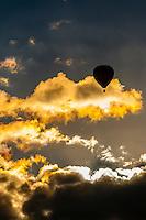 Hot air balloons flying through the clouds at sunrise, Albuquerque International Balloon Fiesta, Albuquerque, New Mexico USA.