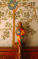 A wooden statue of Christ holds the family crest in his hands
