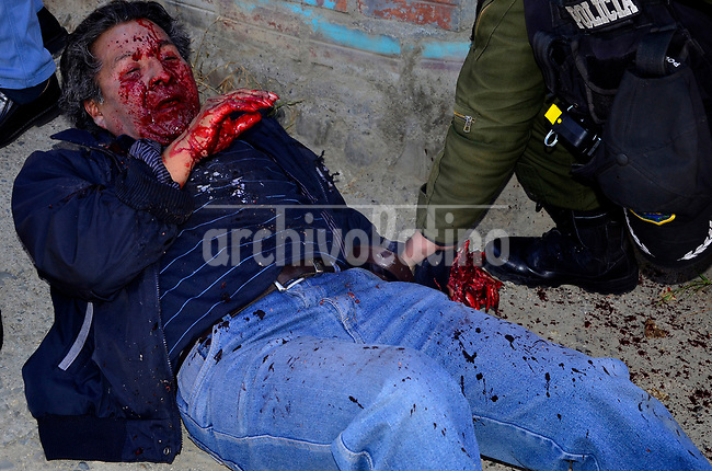 A worker lay at the ground after being bit by a police during a union protest in a textile factory in La Paz