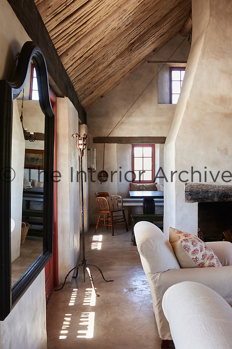 A country sitting room with a central stone fireplace and a wood and bamboo lined pitched roof.