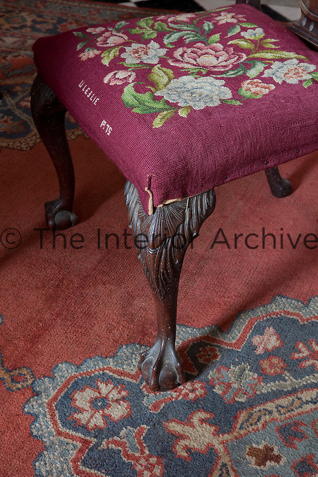 An Irish Georgian chair in the hallway has a tapestry seat, signed Leslie, 1975