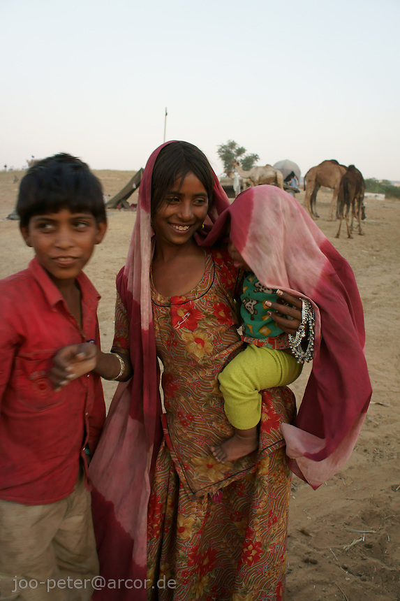 brother and sisiter with baby in desert next to  camel fair in holy city Pushkar while sunset time