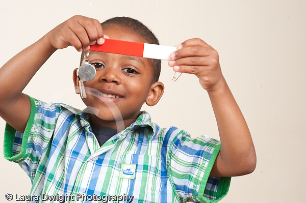 3 year old boy using bar magnet to pick up metal whistle horizontal