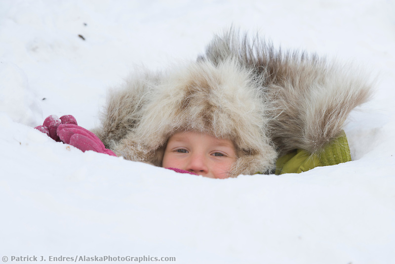 Leo Hicker dressed in a winter parka with a wolf ruff enjoys plays in the snow in Wiseman, Alaska, Arctic