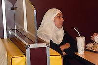 FRANCIA- Parigi - Beurger King Muslim , primo ristorante francese fast food che offre carne hallal, in conformità con i dettami della religione islamica, aperto a fine  luglio 2005 a Clichy sous Bois, banlieu parigina, in una zona  a forte concentrazione musulmana. Si rivolge principalmente alle famiglie, presto verrà creata una catena col marchio BKM in Francia e in Europa.Donna velata seduta al tavolo France- Paris - Beurger King Muslim, the first French restaurant fast food offering halal meat , in accordance with the dictates of the Islamic religion , opened in late July 2005 in Clichy sous Bois , Paris suburbs , in an area with a high Muslim concentration . It caters mainly to families