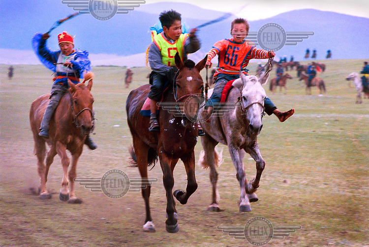 Horse racing during the annual Nadaam festival, Mongolia's most important cultural event. Children between 5 and 12 years old compete on an 18 kilometre track. .The main elements of the festival are the tests of courage, strength and daring through the three 'manly' sports of wrestling, archery and horse racing.