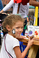 A young girl enjoying a sausage at the block party.