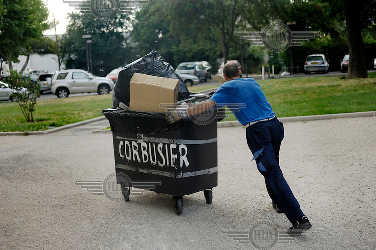 Porter taking out the rubbish from the Unite d'Habitation, the high rise apartment building by modernist architect Le Corbusier.