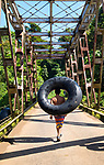 Still wet from riding the rapids of the Sarapiqui river, a Costa Rican boy crosses over the Sarapiqui River Bridge with his rafting tube.  Locals as well as tourists all enjoy rafting on the white water rapids of the Sarapiqui River.